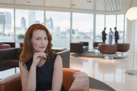 Portrait confident businesswoman with red hair in urban highrise office lounge 11086034013| 写真素材・ストックフォト・画像・イラスト素材|アマナイメージズ