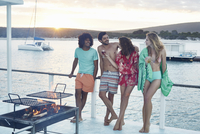 Young adult friends hanging out and drinking on summer houseboat 11086034183| 写真素材・ストックフォト・画像・イラスト素材|アマナイメージズ