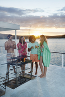 Young adult friends barbecuing, hanging out and drinking on summer houseboat at sunset 11086034187| 写真素材・ストックフォト・画像・イラスト素材|アマナイメージズ