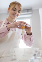 Smiling woman baking, cracking egg over bowl in kitchen 11086034560| 写真素材・ストックフォト・画像・イラスト素材|アマナイメージズ