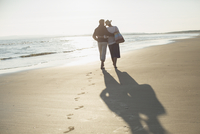 Affectionate mature couple hugging and walking on sunny beach