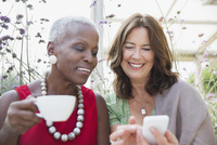 Smiling mature women friends drinking coffee and using cell phone 11086035239| 写真素材・ストックフォト・画像・イラスト素材|アマナイメージズ