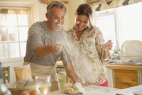 Playful mature couple baking, throwing flour and drinking wine in kitchen 11086035335| 写真素材・ストックフォト・画像・イラスト素材|アマナイメージズ