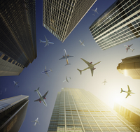 Airplanes in blue sky above highrise buildings, travel concept