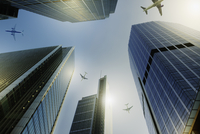 Airplanes flying over highrise buildings, travel concept