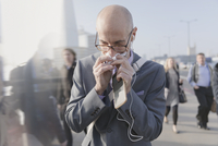 Businessman blowing nose with tissue, holding cell phone and headphones on urban pedestrian bridge