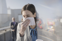 Businesswoman with allergies blowing nose into tissue on sunny urban sidewalk