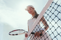 Portrait smiling, confident female tennis player holding tennis racket at net below sunny sky 11086036108| 写真素材・ストックフォト・画像・イラスト素材|アマナイメージズ