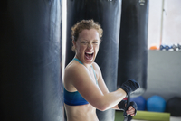 Portrait exuberant female boxer screaming, wrapping wrists in gym 11086036302| 写真素材・ストックフォト・画像・イラスト素材|アマナイメージズ