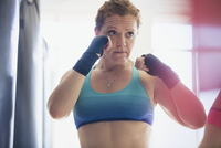 Determined female boxer with wrist wraps in fighting stance at gym 11086036313| 写真素材・ストックフォト・画像・イラスト素材|アマナイメージズ