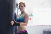 Portrait confident, tough female boxer at punching bag in gym 11086036316| 写真素材・ストックフォト・画像・イラスト素材|アマナイメージズ