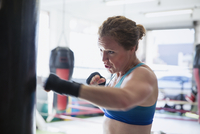 Determined female boxer boxing at punching bag in gym 11086036319| 写真素材・ストックフォト・画像・イラスト素材|アマナイメージズ