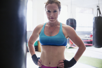 Portrait confident, tough female boxer standing at punching bag in gym 11086036321| 写真素材・ストックフォト・画像・イラスト素材|アマナイメージズ