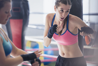 Determined, tough young female boxer shadowboxing in gym 11086036322| 写真素材・ストックフォト・画像・イラスト素材|アマナイメージズ