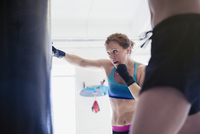 Determined, tough female boxer boxing at punching bag in gym 11086036324| 写真素材・ストックフォト・画像・イラスト素材|アマナイメージズ