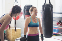 Laughing female boxers next to punching bags in gym 11086036326| 写真素材・ストックフォト・画像・イラスト素材|アマナイメージズ