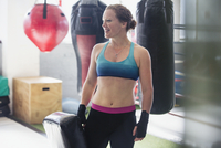 Smiling female boxer standing next to punching bag in gym 11086036329| 写真素材・ストックフォト・画像・イラスト素材|アマナイメージズ