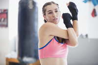Young female boxer stretching shoulder and arms in gym 11086036334| 写真素材・ストックフォト・画像・イラスト素材|アマナイメージズ