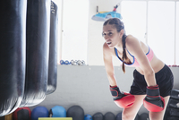 Tired young female boxer resting at punching bags in gym 11086036341| 写真素材・ストックフォト・画像・イラスト素材|アマナイメージズ
