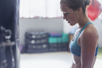 Tired female boxer resting at punching bags in gym 11086036344| 写真素材・ストックフォト・画像・イラスト素材|アマナイメージズ