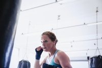 Determined female boxer boxing at punching bag in gym 11086036347| 写真素材・ストックフォト・画像・イラスト素材|アマナイメージズ