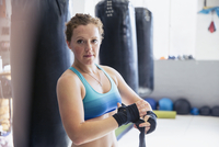 Portrait confident, tough female boxer wrapping wrists next to punching bags in gym 11086036351| 写真素材・ストックフォト・画像・イラスト素材|アマナイメージズ