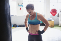 Tired female boxer resting with hands on hips in gym 11086036353| 写真素材・ストックフォト・画像・イラスト素材|アマナイメージズ