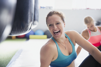 Portrait laughing female boxer stretching in gym 11086036356| 写真素材・ストックフォト・画像・イラスト素材|アマナイメージズ