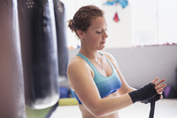 Female boxer wrapping wrists next to punching bag in gym 11086036368| 写真素材・ストックフォト・画像・イラスト素材|アマナイメージズ