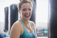 Portrait laughing female boxer standing at punching bag in gym 11086036374| 写真素材・ストックフォト・画像・イラスト素材|アマナイメージズ
