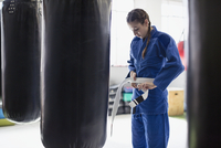 Young woman tying judo belt at punching bags in gym 11086036375| 写真素材・ストックフォト・画像・イラスト素材|アマナイメージズ
