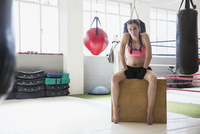 Portrait confident, tough young female boxer resting in gym 11086036378| 写真素材・ストックフォト・画像・イラスト素材|アマナイメージズ