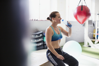 Female boxer drinking water and resting post workout in gym 11086036380| 写真素材・ストックフォト・画像・イラスト素材|アマナイメージズ