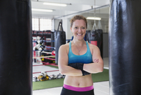 Portrait smiling, confident female boxer standing at punching bags in gym 11086036381| 写真素材・ストックフォト・画像・イラスト素材|アマナイメージズ