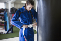 Young woman tightening judo belt at punching bag in gym 11086036385| 写真素材・ストックフォト・画像・イラスト素材|アマナイメージズ