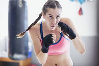 Determined, tough young female boxer shadowboxing in gym 11086036388| 写真素材・ストックフォト・画像・イラスト素材|アマナイメージズ