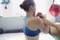 Woman stretching arm and shoulder in gym 11086036389| 写真素材・ストックフォト・画像・イラスト素材|アマナイメージズ