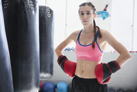Portrait determined, tough young female boxer wearing boxing gloves with hands on hips at punching bags 11086036390| 写真素材・ストックフォト・画像・イラスト素材|アマナイメージズ