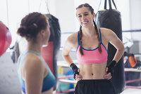 Smiling young female boxers resting in gym 11086036394| 写真素材・ストックフォト・画像・イラスト素材|アマナイメージズ