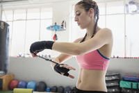 Young female boxer wrapping wrists in gym 11086036396| 写真素材・ストックフォト・画像・イラスト素材|アマナイメージズ