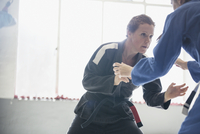 Determined, tough woman practicing judo in gym 11086036398| 写真素材・ストックフォト・画像・イラスト素材|アマナイメージズ
