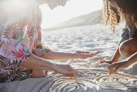 Mother and daughter drawing spirals in the sand on sunny summer beach