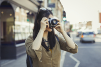 Young female tourist photographing with camera on urban street 11086037257| 写真素材・ストックフォト・画像・イラスト素材|アマナイメージズ