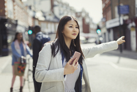 Young businesswoman with cell phone hailing taxi on sunny urban street 11086037267| 写真素材・ストックフォト・画像・イラスト素材|アマナイメージズ