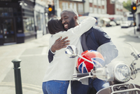 Affectionate young couple hugging at motor scooter on sunny urban street 11086037291| 写真素材・ストックフォト・画像・イラスト素材|アマナイメージズ