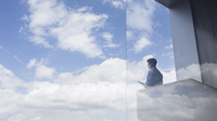 Pensive businessman standing on modern balcony looking at blue sky and clouds 11086037634| 写真素材・ストックフォト・画像・イラスト素材|アマナイメージズ