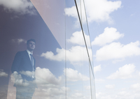 Businessman looking out modern office window at blue sky and clouds 11086037653| 写真素材・ストックフォト・画像・イラスト素材|アマナイメージズ