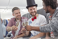 Young male friends toasting champagne glasses on airplane 11086037911| 写真素材・ストックフォト・画像・イラスト素材|アマナイメージズ