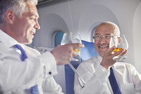 Businessman toasting whiskey glasses in first class on airplane 11086037926| 写真素材・ストックフォト・画像・イラスト素材|アマナイメージズ