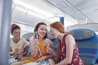 Young women friends laughing, drinking champagne in first class on airplane 11086037967| 写真素材・ストックフォト・画像・イラスト素材|アマナイメージズ